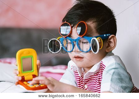 Kid wearing eye glasses playing the toy with fun.