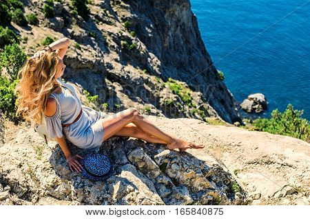 Beautiful woman sitting on a rock near blue sea on resort