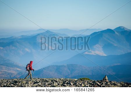 Male Backpaker Walking On The Rocky Top Of The Mountain