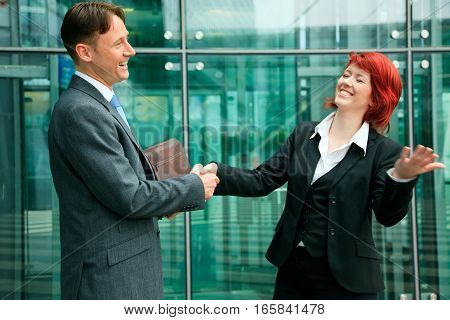 business people in front of an office building, shaking hands