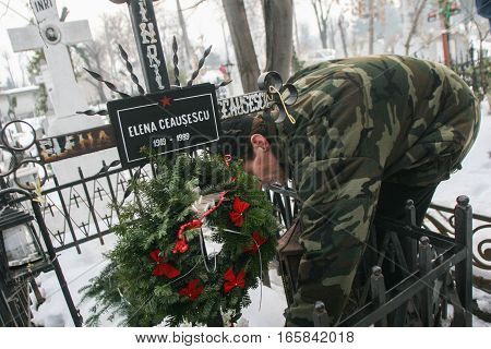Bucharest Romania December 25 2009: A man lights a candle at the grave of Elena Ceausescu during commemoration of her death. Year after year Romania's nostalgic Communists gather to mourn Ceausescu who was executed on Christmas Day together with his wife