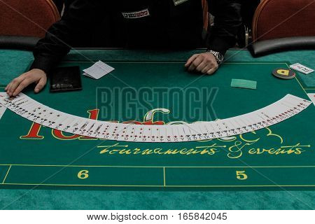 Bucharest Romania December 19 2015: A croupier arranges cards in a poker festival organized in Bucharest.
