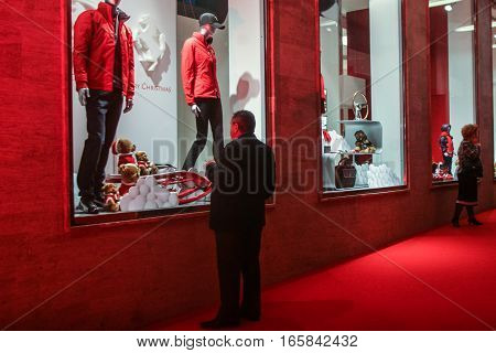 Bucharest Romania December 5 2009: A man is looking at the products displayed in the window of the Ferrari showroom in Bucharest.