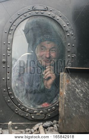 Brad Romania December12 2009: A mechanic is seen through an window in an old steamed cog train in Brad on winter holydays.