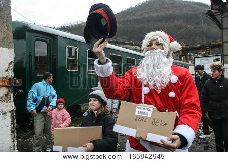 Brad Romania December12 2009: A man dressed in Santa Claus shares sweets to the tourists which are travel in an old steamed cog train in Brad on winter holydays.