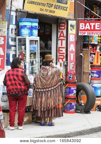 La Paz Bolivia - December 12 2016: Two Bolivian women stand in front of battery store in La Paz Bolivia on December 12 2016