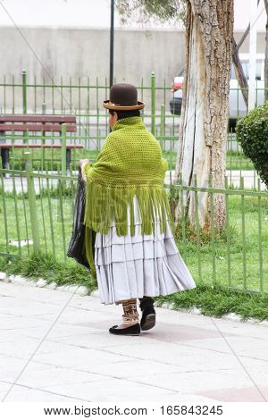 La Paz Bolivia - December 12 2016: Woman in traditional dress and bowler hat walks in park in La Paz Bolivia on December 12 2016