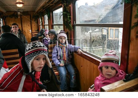 Brad Romania December12 2009: Children are travel in an old steamed cog train in Brad on winter holydays.