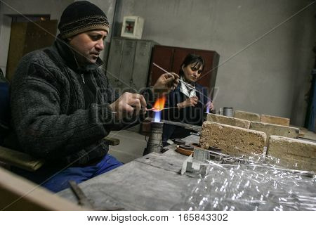 Curtea de Arges Romania December 14 2009: A man and a woman are manufacturing glass Christmas balls in Argocoms Glass factory in Curtea de Arges.