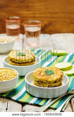 Zucchini lentils oats parsley fritters on wood background