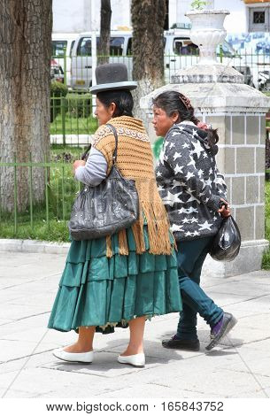 La Paz Bolivia - December 12 2016: Woman in traditional dress and bowler hat walks with daughter in La Paz Bolivia on December 12 2016