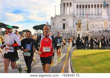 ROME, ITALY: December 31, 2016 : athletes participating in the Rome Marathon while crossing Piazza Venezia, in the background the famous Vittoriano monument on December 31, 2016, Rome, Italy