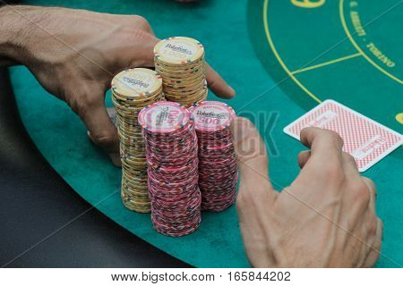 Bucharest Romania December 19 2015: Gamblers are playing poker with chips and cards in a poker festival organized in Bucharest.