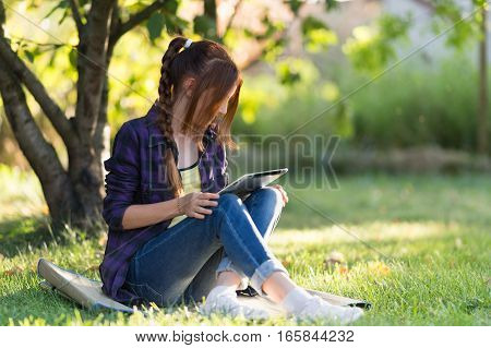 Girl in jeans sitting on the grass in the garden with your tablet