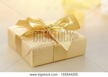 Valentines day gift. Golden box covered with gold foil, ribbon with bow.