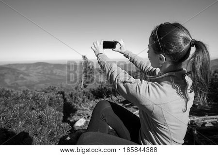 Young Woman Hiker Taking Photo With Cell Phone