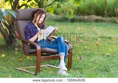 Teen girl in jeans is sitting in a chair in the garden with a book