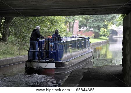 Couple navigating a narrow boat on the Llangollen Canal in Wales.