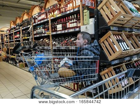 Bucharest Romania December 26 2015: A child in a cart is seen in the wine area in a supermarket in Bucharest.