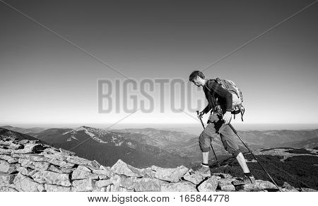Man Backpacker Walking On The Rocky Ridge Of The Mountain