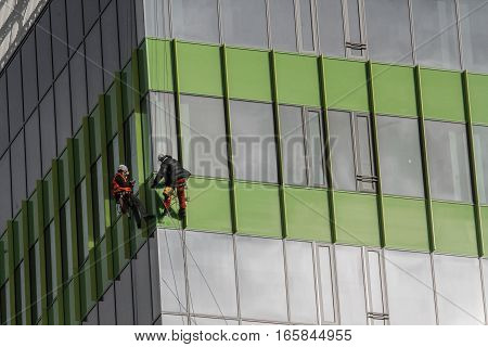 Bucharest Romania December 2 2015: Laborers are cleaning the windows of an office building in a business district in Bucharest.