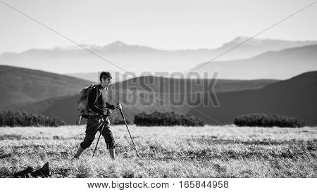 Backpacker Walking On Plato Of The Mountain With Trekking Sticks