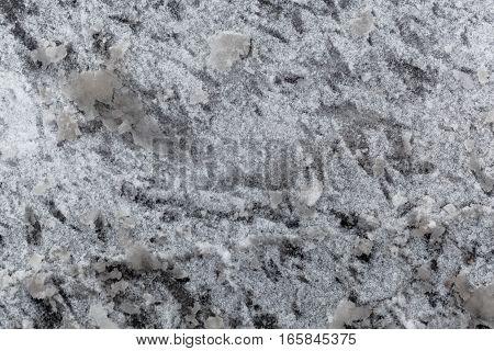 Snow slush on a paved road side.