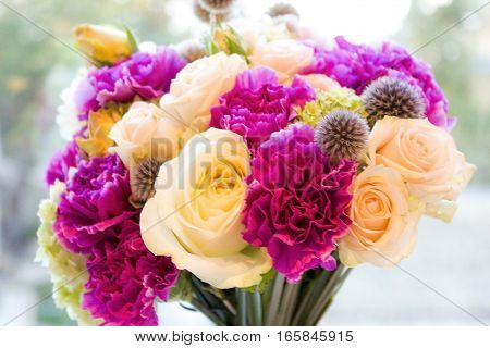 bridal bouquet of purple and white flowers in a hand of the girl