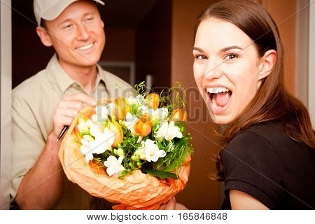 a delivery boy is hading over a bouquet of flowers to a young female customer. focus is on the girl.