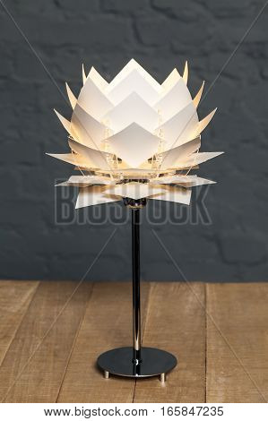 Front view of white conceptual table lamp on wooden stand on gray brick wall background