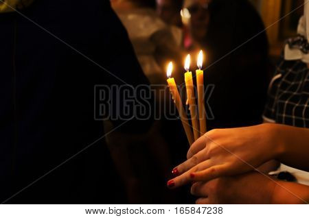 three church candles in their hands in the Russian Orthodox Church
