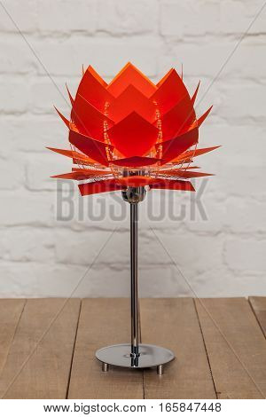 Front view of red conceptual table lamp on wooden stand on white brick wall background
