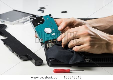 Cleaning computer hardware with cloth. Person performs service maintenance of hard disc of portable PC after dismantling it on white table