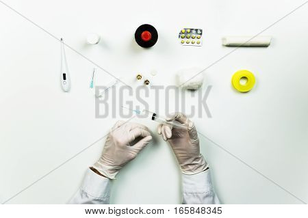 Medical doctor working place flat lay. Top view of hands of MD holding syringe ready for injection on table with medical utensils