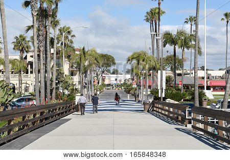 NEWPORT BEACH CALIFORNIA - JANUARY 6 2017: Balboa Pier looking towards the boardwalk. The Balboa Peninsula is a popular destination for tourists and locals.