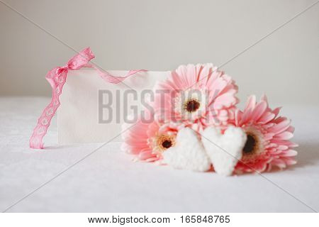 Valentine's Day symbols tender pink gerbera flowers and heart shaped coconut candies