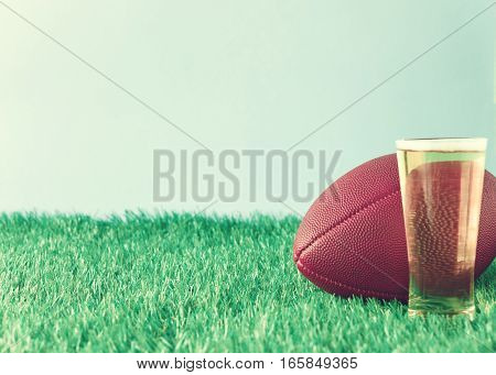 Vintage football over grass and beer glass