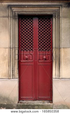 A red iron door with door knobs and a hole pattern. It is rectangle, closed and has an ornate frame. Its texture is made of a pattern of steel crosses.