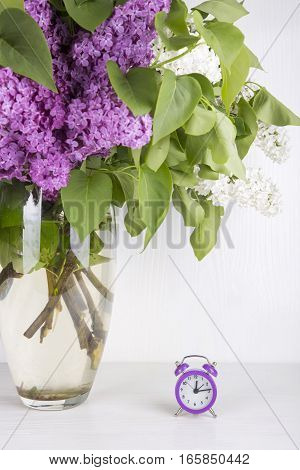 Bouquet Of Lilac With Purple Alarm Clock On White Background
