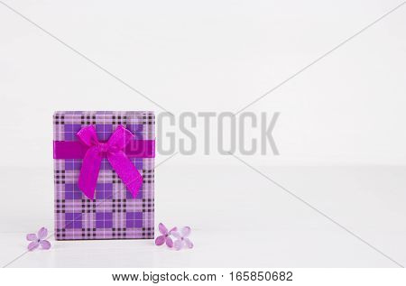 Purple Gift Box Surrounded By Lilac Flowers On White Background