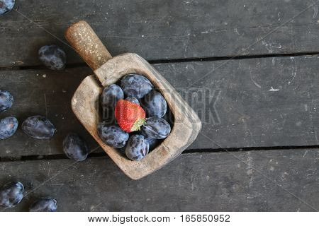 Plums on an old rustic table. Vintage style.