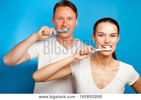 a man and a young woman are brushing their teeth in front of a blue background