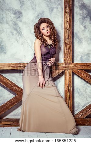 Fashion model with long dress and curly hairstyle and makeup posing near wall with wooden pole. studio shot.