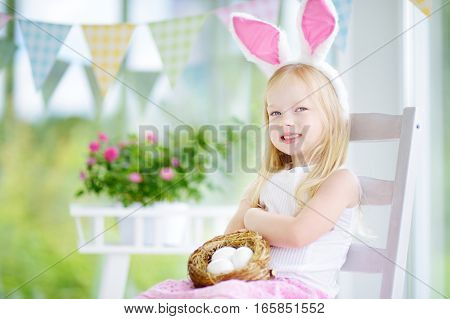 Cute Little Girl Wearing Bunny Ears Playing Egg Hunt On Easter