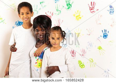 studio shot of african mother and her children painting.