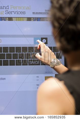 Woman at shopping mall looking for directions on a digital directory board
