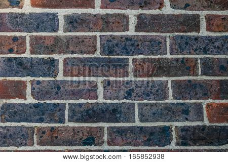Brick wall of Ockley double diamond stock bricks.  Reds and purples with a lime mortar pointing