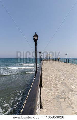 Long pier at Amathus, Limassol, Cyprus. Shows the pier with an arbor at the end and a lone fisherman. The sea is rough with waves.