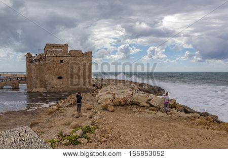 Paphos castle on a stormy day. Stormy summer's day with cloudy sky and crashing waves.