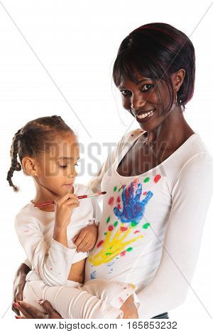 studio shot of african mother and her daughter painting on her shirt.
